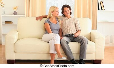 Happy young couple on the sofa figh