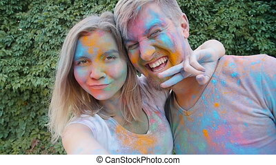 Happy young couple playing with colorful paints