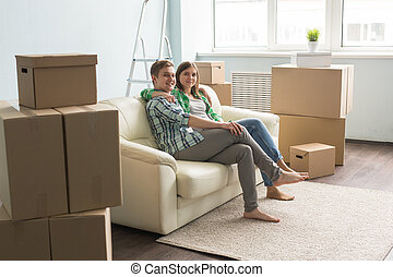 Happy young couple posing on sofa between boxes in a new house.