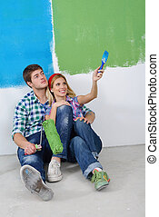 happy young couple relaxing after painting in new home