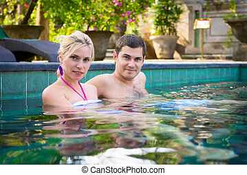 Happy young couple relaxing in a swimming pool