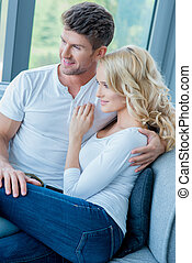 Happy young couple relaxing on a couch at home