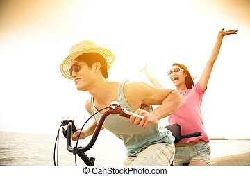 happy young couple riding bicycle on the beach
