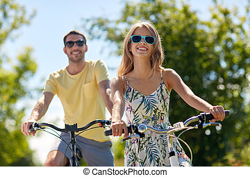 happy young couple riding bicycles in summer - people,...