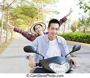 happy young couple riding scooter in town