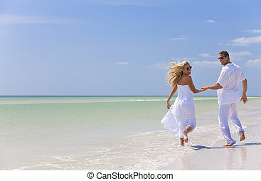 Happy Young Couple Running Holding Hands on A Tropical Beach...