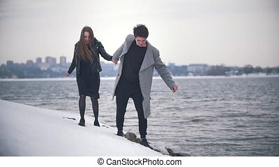 Happy young couple running on the snowy riverside in cloudy...