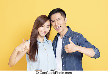 happy young couple showing the thumbs up