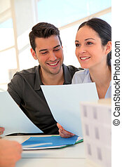 Happy young couple signing property purchase contract