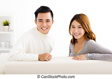 happy young couple sitting in sofa