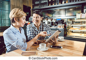 Happy young couple sitting in the coffee shop
