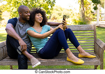 Happy young couple sitting on a bench in the garden