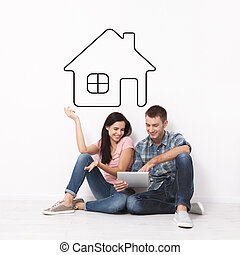 Happy young couple sitting on floor using a tablet for shopping and entertainment. Layout. Drawing house as a background.