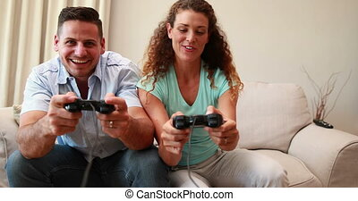 Happy young couple sitting on sofa