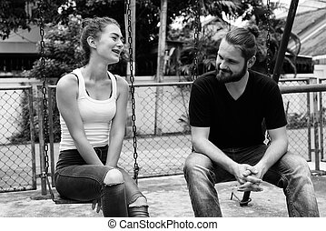 Happy young couple smiling and sitting on the metal swings together in the old playground