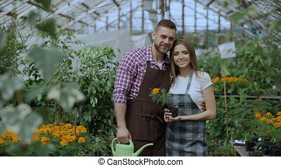 Happy young couple smiling in greenhouse. Attractive woman...