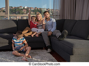 happy young couple spending time with kids at home