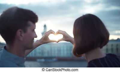 Happy young couple standing at sunset making a heart shape with their hands
