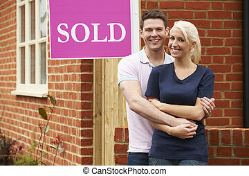 Happy Young Couple Standing Next to Sold Sign Outside New Home