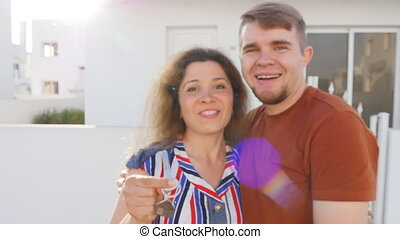 Happy young couple standing outdoors holding key to their new house