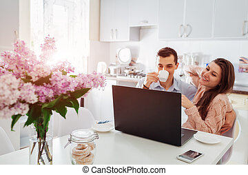 Happy young couple using laptop while having breakfast in modern kitchen. Young man and woman drink coffee and smile