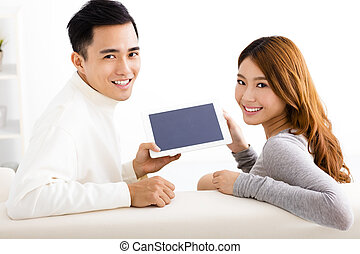 happy Young couple using  tablet on sofa
