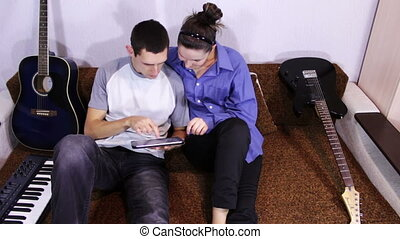 Happy Young Couple using Tablet PC on the couch