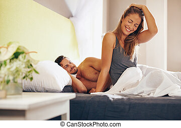 Happy young couple waking up in the morning on bed