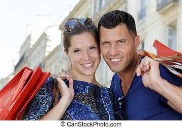 happy young couple walking in the city after shopping