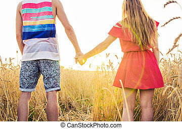 Happy young couple walking on wheat field.