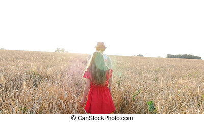 Happy young couple walking together through wheat field