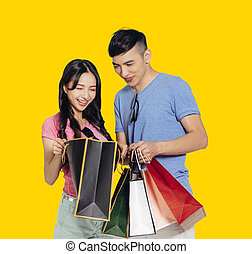 Happy young couple watching the gift in  shopping bags