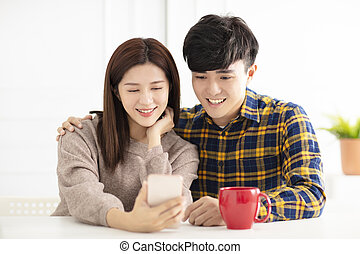 Happy young couple watching the smart phone