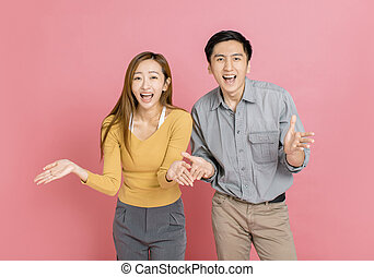 Happy young couple with arms up celebrating