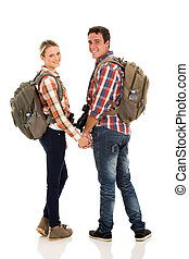 young couple with backpacks looking back - happy young...