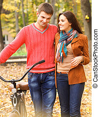 Happy young couple with bicycle in autumn park - Happy young...