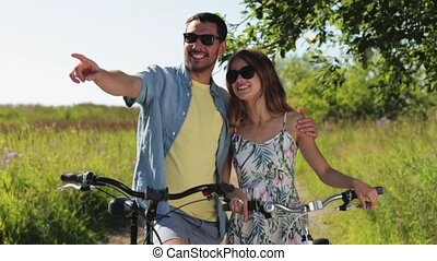 happy young couple with bicycles in summer