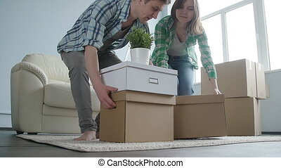 Happy young couple with cardboard boxes moves to new...
