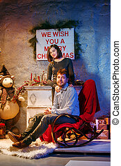 Happy young couple with Christmasd ecorations tree at home