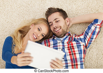 Happy young couple with contemporary digital tablet on carpet