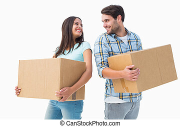 Happy young couple with moving boxe