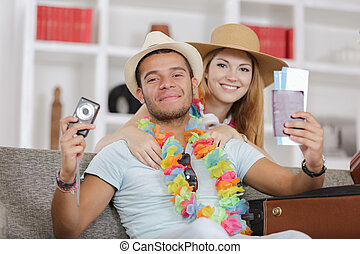happy young couple with passports camera and tickets