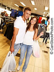 Happy young couple with shopping bags in sportswear store