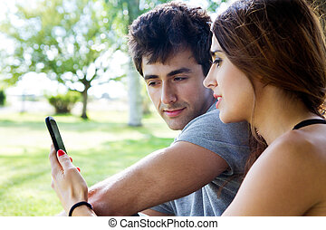 happy young couple with smartphone at the park