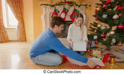 Happy young couple wrapping Christmas presents and kissing