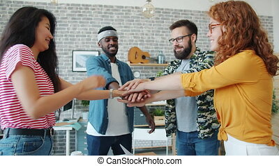 Happy young coworkers multi-ethnic team is putting arms together in office expressing positive emotions enjoying teamwork. People, connection and job concept.