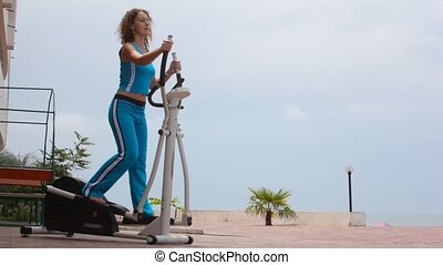 happy young curly-headed woman on training apparatus outdoor