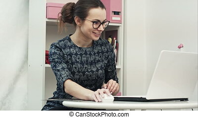Happy young designer consult and offer new clothes to a forein customer having online conference with a laptop computer