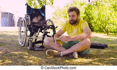 Happy young disable man sitting on the grass in the park