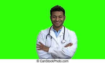 Happy young doctor crossed arms on green screen.